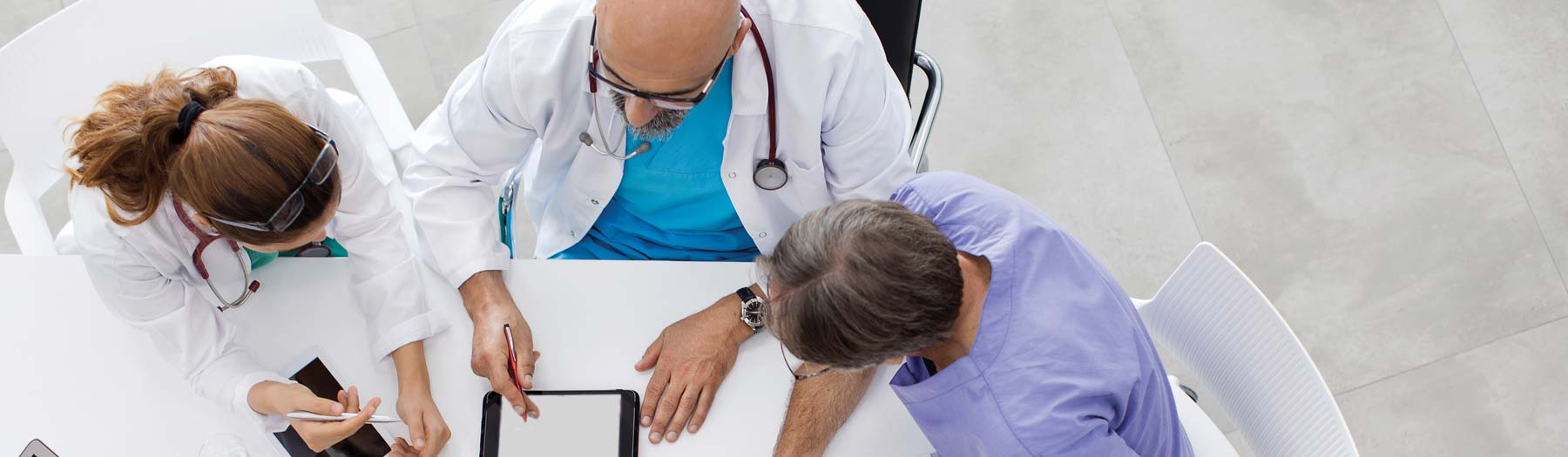 Doctors at Table looking at tablet